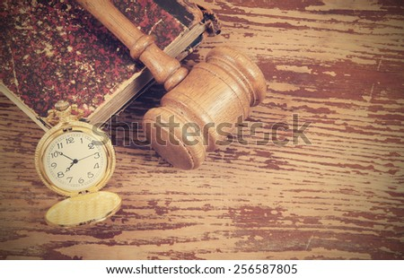 Judge's gavel, legal book and watch on old wooden background