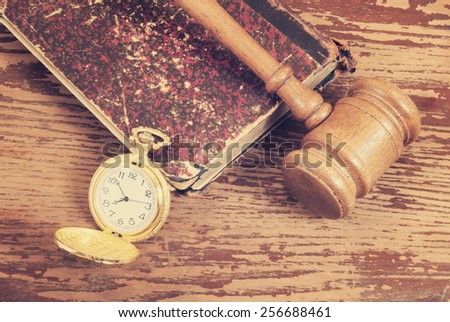 Judge's gavel, legal book and watch on old wooden background - stock photo