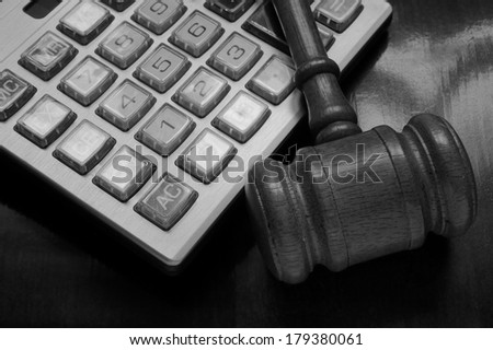 Judge's gavel on calculator, arbitration concept