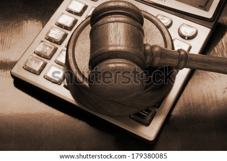 Judge's gavel on calculator, arbitration concept - stock photo