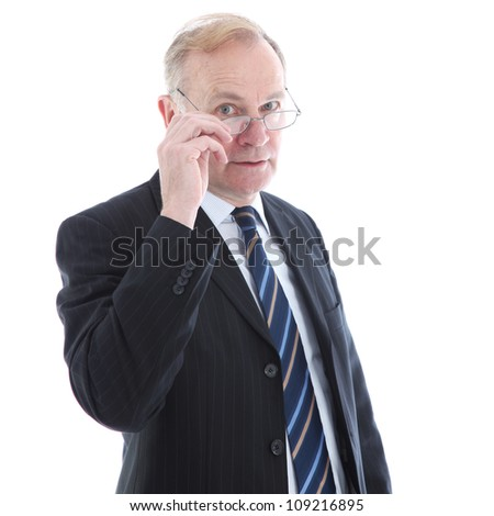 Judgemental elderly businessman Judgemental elderly business executive peering over the top of his glasses with a serious watchful expression