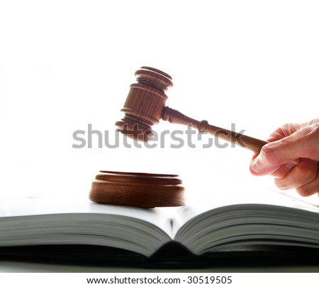 judges court gavel being pounded on a law book, on white background - stock photo