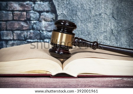 judges gavel and  book on wall background - stock photo