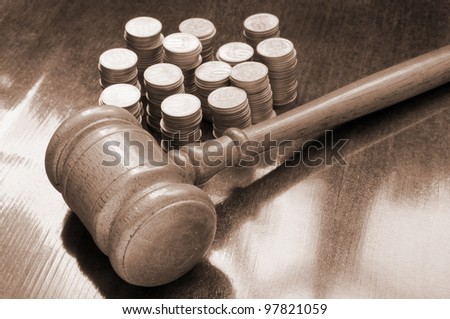 Judges gavel and coins on wooden table - stock photo