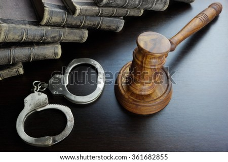 Judges Gavel, Handcuffs And Old Law Book  On The Black Wooden Table Background In The Back Light. Overhead View. Lawsuit or Bail Or Arrest Concept - stock photo