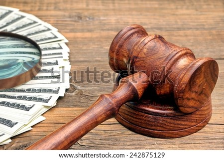 Judges Gavel, Money and Magnifying Glass on Wood Table - stock photo