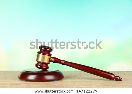 Judges gavel on wooden table on light background - stock photo