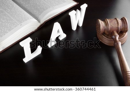 Judges Gavel, Red Open Legal Book And White Sign LAW From Wood Latter On The Black Table In The Back Light. Overhead View.