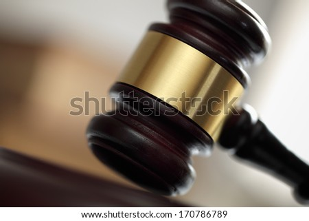 Judges hitting wooden gavel in courtroom - stock photo