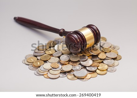 judges law gavel on pile of coins isolated on gray - stock photo