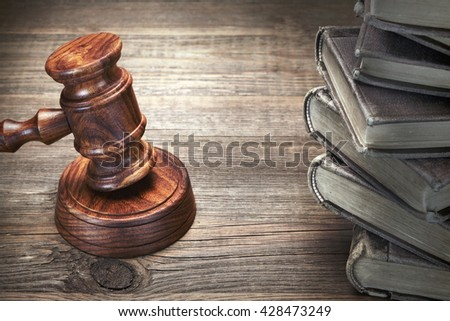 Judges Or Auctioneer Gavel And Old Law Books On The Rough Wooden Table In The Background. Law Concept. Top View - stock photo