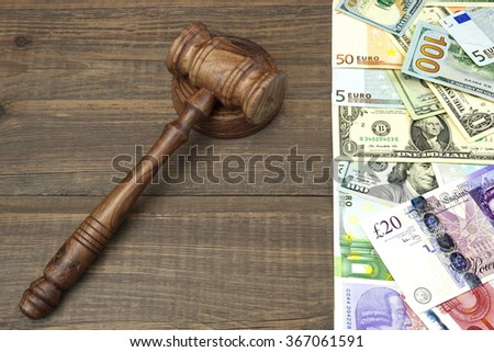 Judges Or Auctioneers Gavel And International Cash - Dollars, Euro, Pounds On Rough Brown Wood Table Background With Space For Text Or Image - stock photo