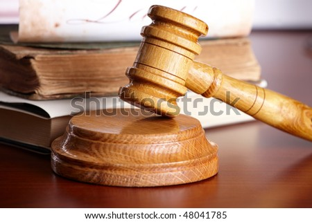 Judges wooden gavel with very old books and paper with word law in the background. - stock photo
