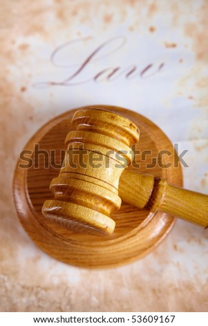 Judges wooden gavel with very old paper with word law in the background. - stock photo