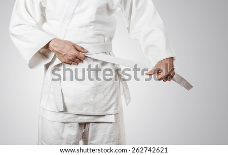 Judoka tying the white belt (obi) - stock photo