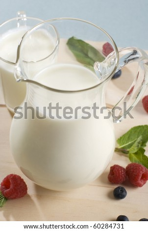 Jug and a milk mug and berries