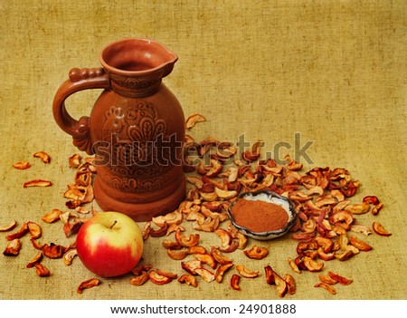 Jug, apple, cinnamon and dessicated fruit on flax background - stock photo
