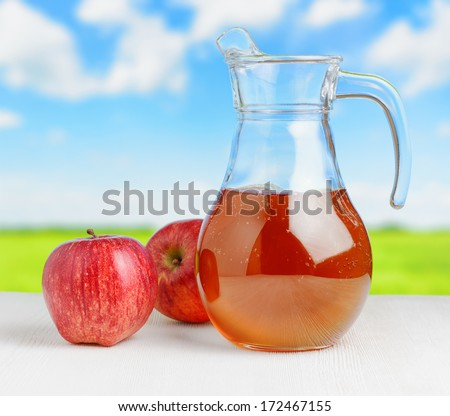 Jug of apple juice on nature background. Half full pitcher. - stock photo