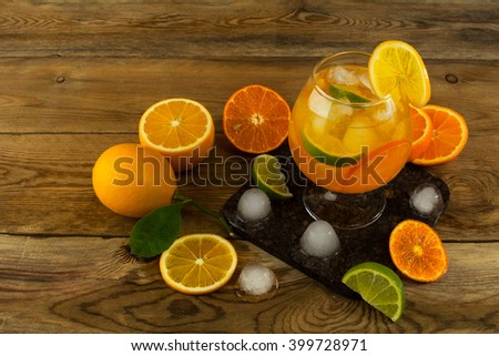 Jug of cool fruit cocktail on wooden table. Fruit cocktail. Fruit drink. Fruit lemonade. Summer drink Citrus lemonade - stock photo
