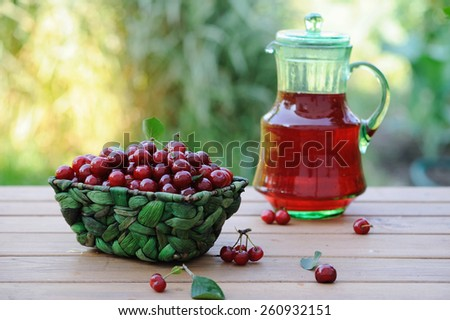 Jug of juice and basket with ripe cherries on wooden table outdoor - stock photo