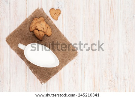 Jug of milk and heart shaped cookies on white wooden table with copy space - stock photo