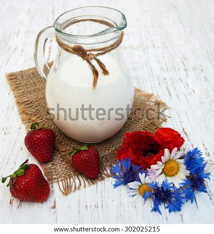 Jug of milk, strawberries and wildflowers on a old wooden background - stock photo