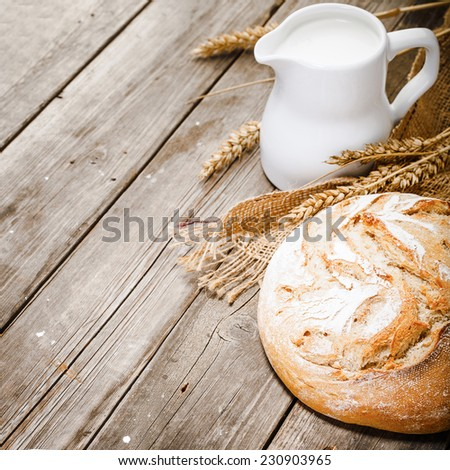 jug of milk, white bread, rye and sacking on wooden table - stock photo