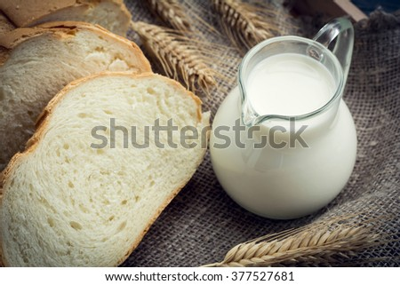 Jug of milk with sliced white bread and wheat ears on linen texture