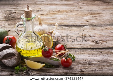 Jug of olive oil, pasta, tomatoes, herbs, salt, pepper, ingredients for cooking on a simple wooden kitchen table. selective focus - stock photo