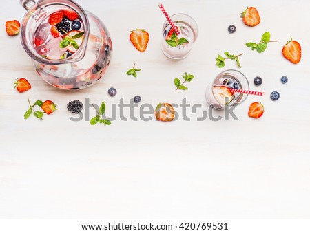 Jug with berries water , ice cubes, Glasses  and ingredients on  white wooden background, top view. Healthy summer drink.