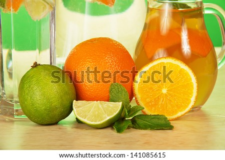 Jug with drink, a glass, a juicy lime and oranges, closeup on a table - stock photo