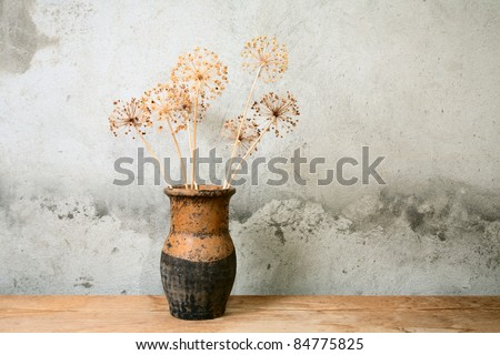 jug with dry flower on a wooden table - stock photo