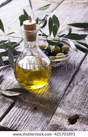 Jug with extra virgin olive oil on olive cutting board surrounded by branches of the olive tree and olives. Selective focus. The concept of a healthy natural food. Selective focus - stock photo
