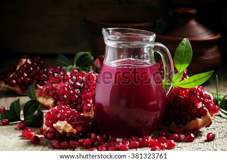 Jug with fresh pomegranate juice on the background of open grenade on dark wooden background, selective focus - stock photo