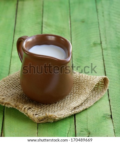 jug with milk on wooden table rustic still life - stock photo