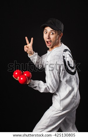 Juggler with red and white balls at black background