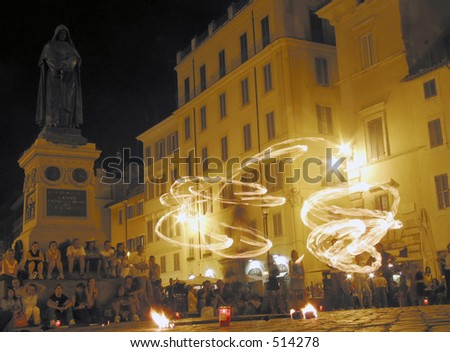 Jugglers with fire, in the square of flowers (campo dei fiori) in rome italy with the statue of Giordano Bruno (a philosopher who was set on fire in this square by the church for his thoughts)