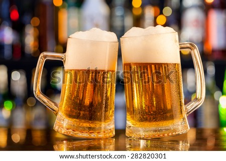 Jugs of beer placed on bar counter with copy space