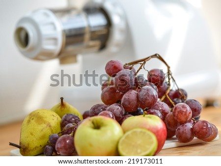 Juice extractor preparation with vegetables and fruits in white kitchen - stock photo