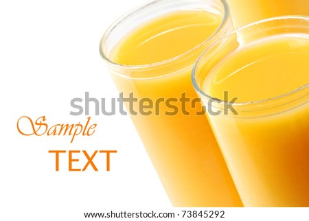 Juice glasses filled with freshly squeezed orange juice on white background with copy space.  Macro with shallow dof. - stock photo