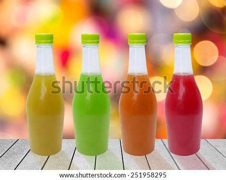 Juice in a plastic bottle is placed on wood backdrop Abstract colourful Bokeh.