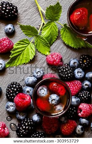 Juice of wild berries on a dark background, top view, selective focus - stock photo
