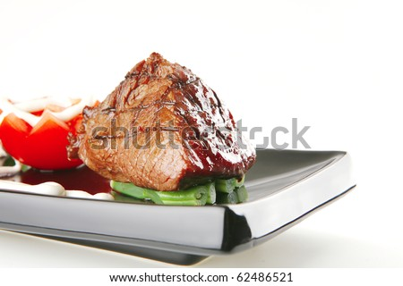 juice roast fillet mignon served on a black plate with tomato - stock photo