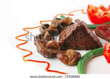 juice roast fillet mignon served on a white plate with tomatoes - stock photo