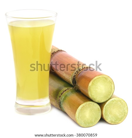Juice with pieces of sugarcane over white background - stock photo