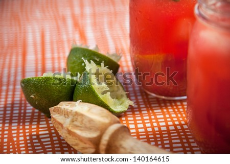 Juiced Limes with a wooden juicer sitting next to margaritas on an orange striped table cloth - stock photo