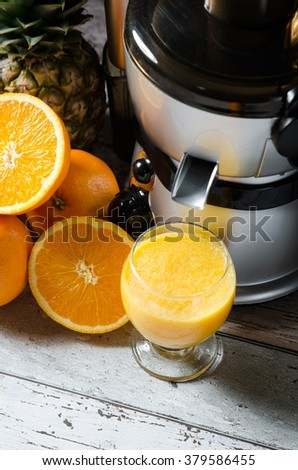 Juicer and orange juice in glass on wooden desk. Fruits in background - stock photo