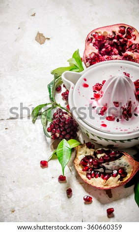 Juicer with bits of pomegranates and leaves. On rustic background.