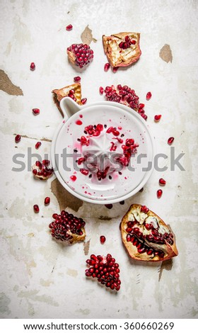 Juicer with slices of pomegranate. On the rustic background. Top view - stock photo