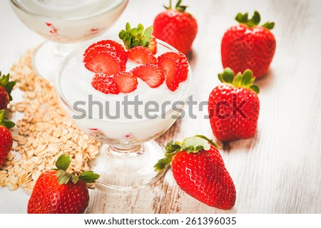 Juicy and healthy strawberries with breakfast cereals for breakfast, on a wooden white table - stock photo